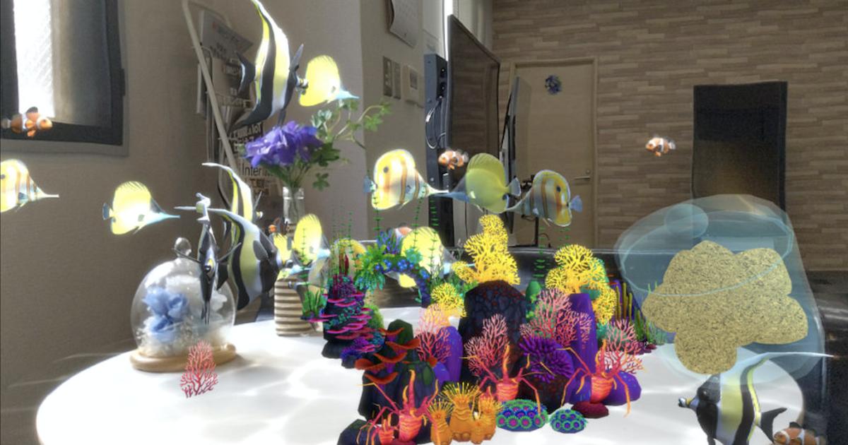 サンゴで飾られたデスク周りで泳ぐ魚たち